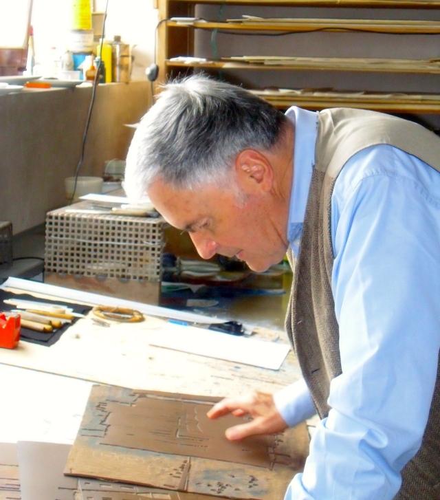 Der Künstler beugt sich in seinem Atelier über eine schon geschnittene Linolplatte
